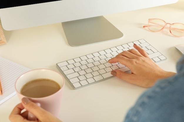 Vrouw die aan moderne computer op witte lijst werkt