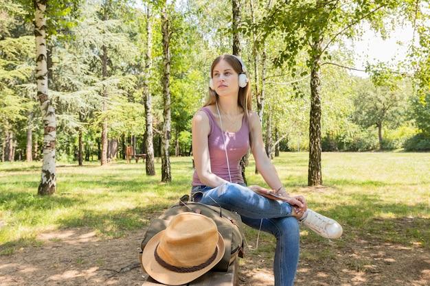 Vrouw die aan muziek in het bos luistert