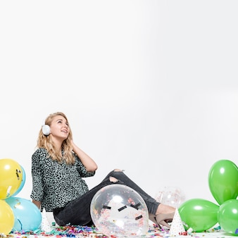 Vrouw die aan muziek luistert die door ballons wordt omringd