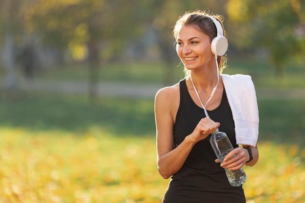Vrouw die aan muziek luistert en een fles water houdt