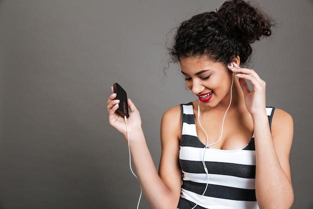Vrouw die aan muziek luistert en oortelefoons gebruikt