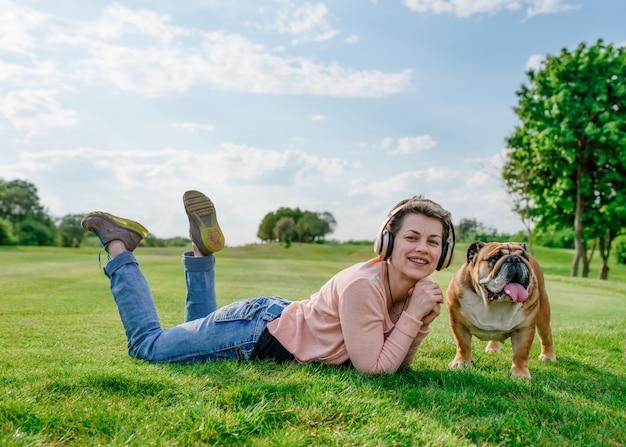 Vrouw die aan muziek luistert of audioboek en op groen gras met hond in het park rust