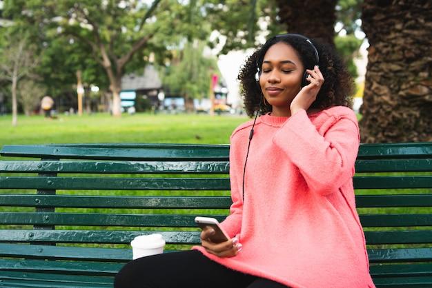 Vrouw die aan muziek met haar telefoon luistert