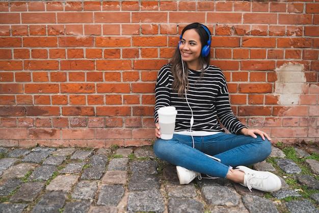Vrouw die aan muziek met kop van koffie luistert.