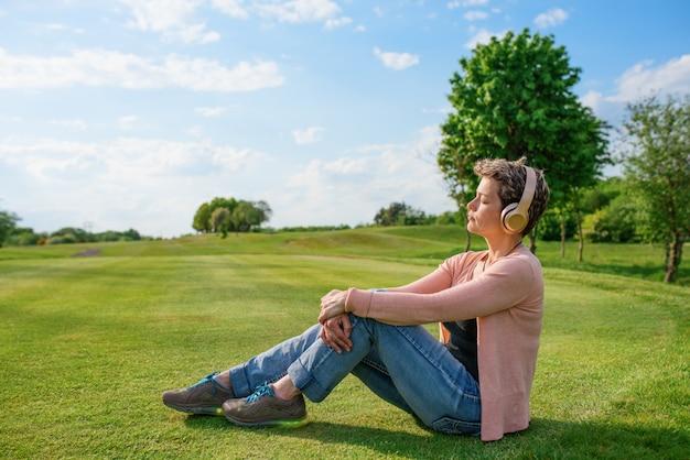 Vrouw die aan muziek of audioboek luistert en zet en op groen gras rust
