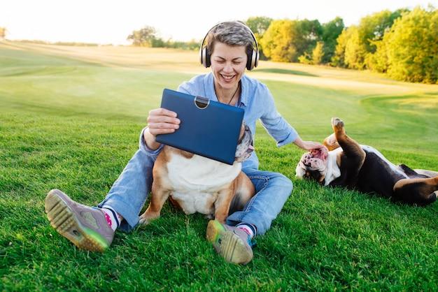 Vrouw die aan muziek of audioboek luistert, video op tablet bekijkt en op weide met twee honden / buldoggen in het park rust