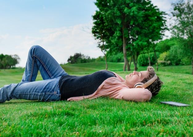 Vrouw die aan muziek of luisterboek luistert en en op groen gras in het park ligt rust