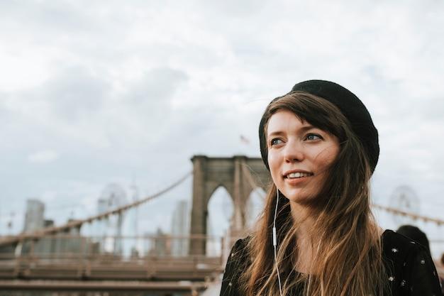 Vrouw die aan muziek op de brug van brooklyn, de vs luisteren