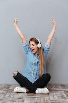 Vrouw die aan muziek op de vloer luistert