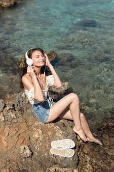 Vrouw die aan muziek op een rots luistert