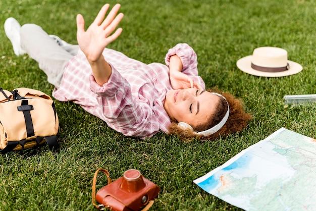 Vrouw die aan muziek op hoofdtelefoon op de grond luistert