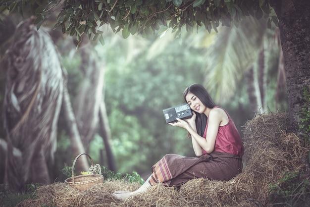 Vrouw die aan radio in platteland luistert