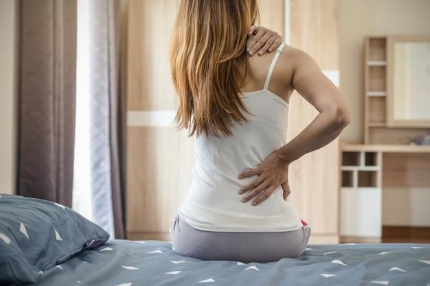 Vrouw die aan rugpijn op het bed lijden