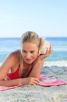 Vrouw die aan shell luistert