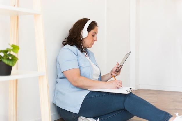 Vrouw die aan tablet van huis werkt