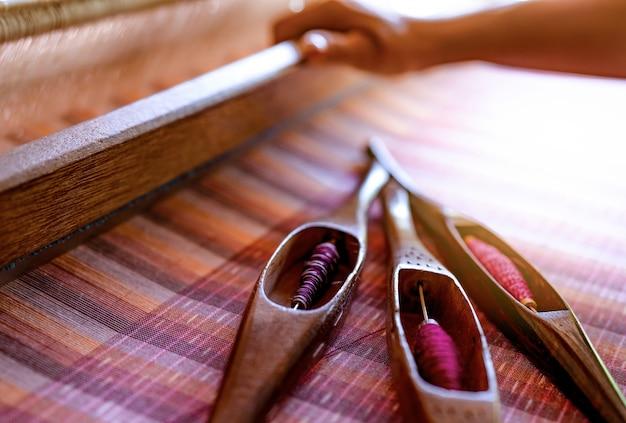 Vrouw die aan wevende machine werkt voor het weven van met de hand gemaakte stof. textiel weven. weven met traditioneel handweefgetouw op katoenen draden.