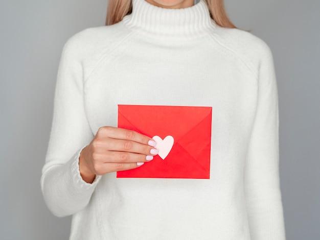 Vrouw die aanbiddelijke valentijnskaartenvelop houdt