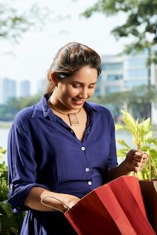 Vrouw die aankopen in papieren zak controleert