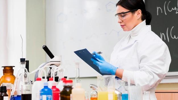 Vrouw die aantekeningen in laboratorium maakt