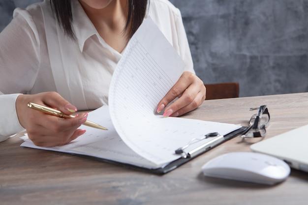 Vrouw die aantekeningen maakt in papieren