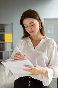 Vrouw die aantekeningen maakt op haar notitieboekje op het werk