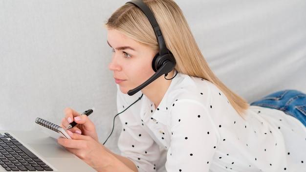 Vrouw die aantekeningen maakt van online cursus