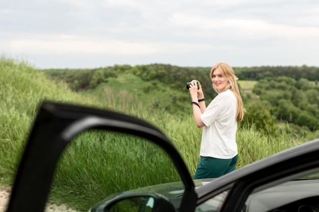Vrouw die aardbeelden voor auto neemt