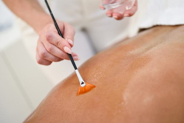 Vrouw die achtermassagebehandeling met olieborstel ontvangt