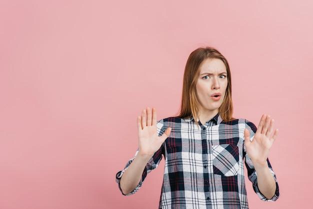 Vrouw die afstand met roze achtergrond maakt
