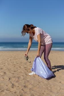 Vrouw die afval en plastieken opnemen die het strand schoonmaken
