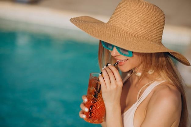 Vrouw die alcoholcocktail drinkt bij het zwembad
