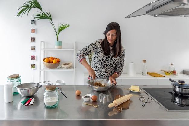 Vrouw die alle ingrediënten voor een dessertrecept in een kom mengt