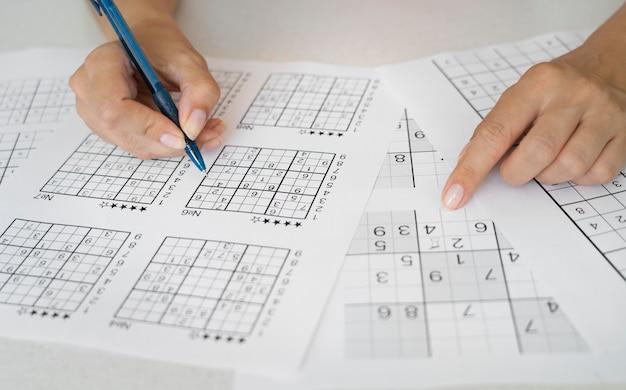 Vrouw die alleen geniet van een sudoku-spel