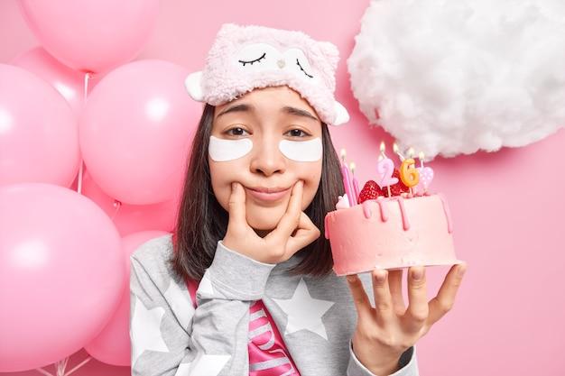 Vrouw die alleen is heeft een slecht humeur op verjaardag houdt vingers bij mondhoeken dwingt glimlach gekleed in slaappak