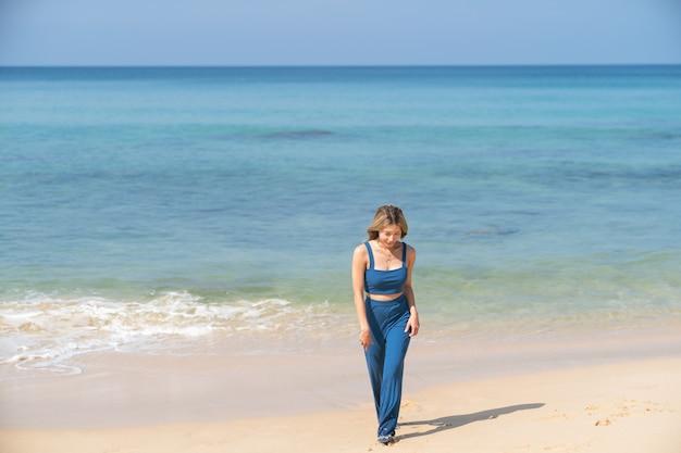 Vrouw die alleen op het strand loopt. strand zomervakantie vakantie.