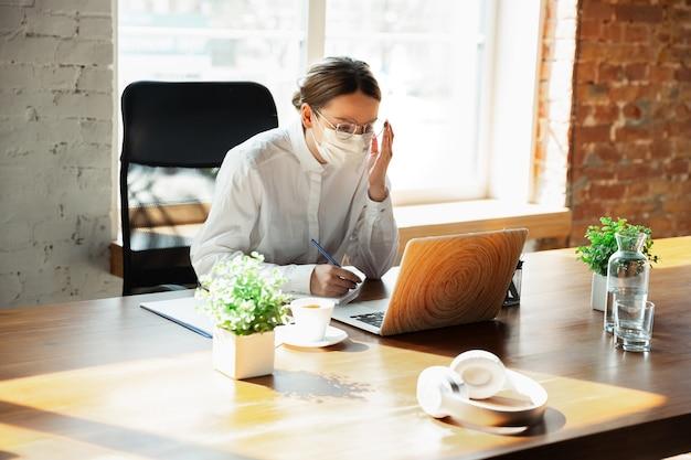 Vrouw die alleen op kantoor werkt tijdens coronavirus of covid-19 quarantaine, gezichtsmasker draagt