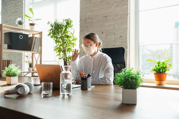 Vrouw die alleen op kantoor werkt tijdens coronavirus of covid-19 quarantaine, met gezichtsmasker