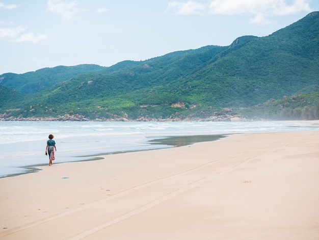 Vrouw die alleen op woestijnstrand loopt. quy hoa reisbestemming quy nhon vietnam, centrale kust tussen da nang en nha trang. prachtige zand baai wuivende oceaan