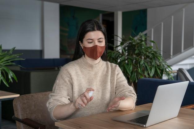 Vrouw die alleen werkt terwijl ze sociaal afstand neemt van andere collega's