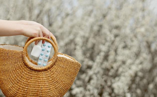 Vrouw die allergiepillen in een zak zet