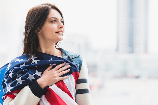 Vrouw die amerikaanse vlag op hart drukt