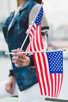 Vrouw die amerikaanse vlaggen op onafhankelijkheidsdag houdt