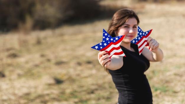 Vrouw die amerikaanse vlagsterren houdt en camera bekijkt