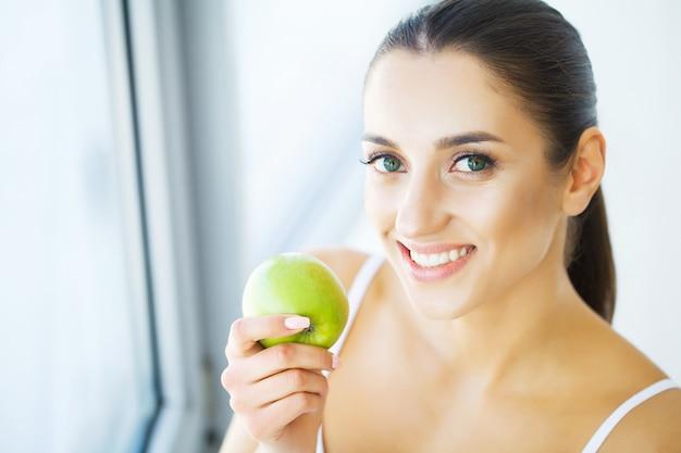 Vrouw die appel eet. mooi meisje met witte tanden bijten apple. beeld