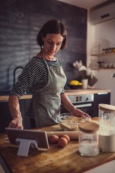 Vrouw die appeltaartrecept op de tablet zoeken