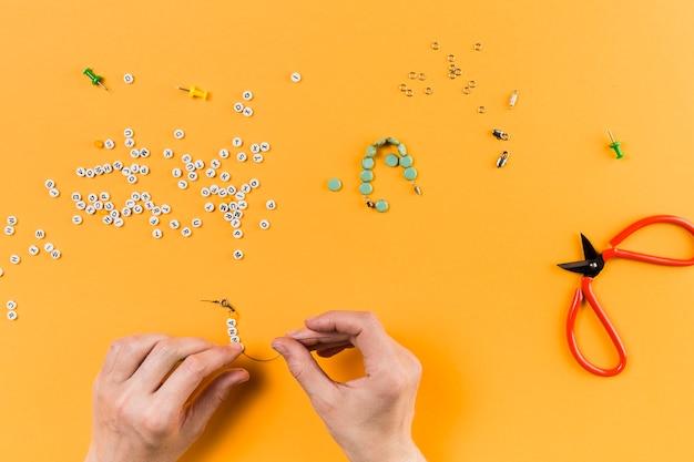 Vrouw die armband van brievenparels op gele achtergrond maakt