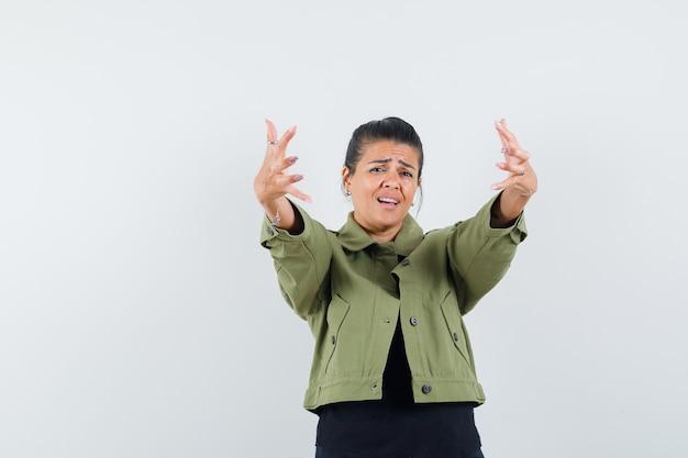 Vrouw die armen opent voor knuffel in jasje, t-shirt en er optimistisch uitziet