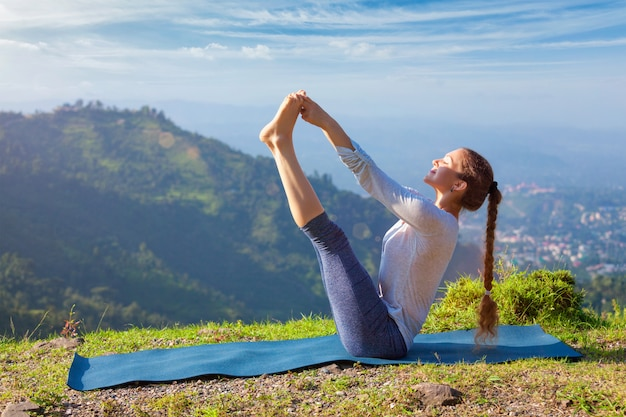 Vrouw die ashtanga vinyasa yoga asana in openlucht doet