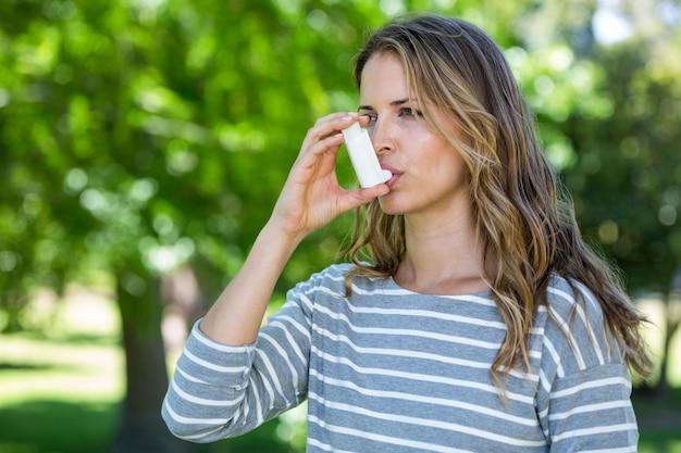Vrouw die astma-inhalator met behulp van
