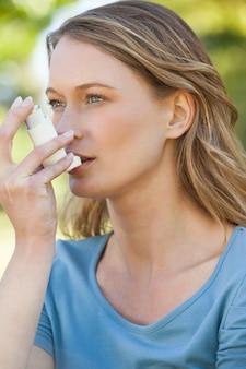 Vrouw die astmainhaleertoestel in het park gebruikt